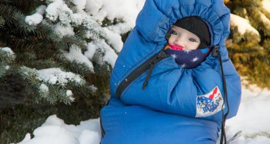 Photo d'un bébé dans un sac-anorak en hiver sous la neige Jewpop