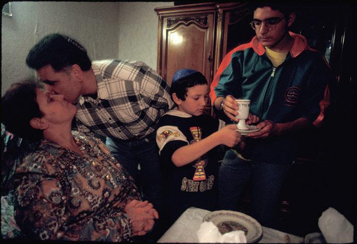Photo représentant une famille juive tunisienne de Sarcelles, repas de Shabbat, la bénédiction du kiddoush