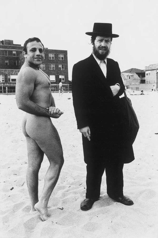 Photo représentant un culturiste juif naturite avec un Hassid sur la plage de Coney Island Jewpop