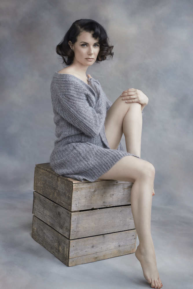 Photo représentant l'actrice Mia Kirshner assise sur une caisse Jewpop
